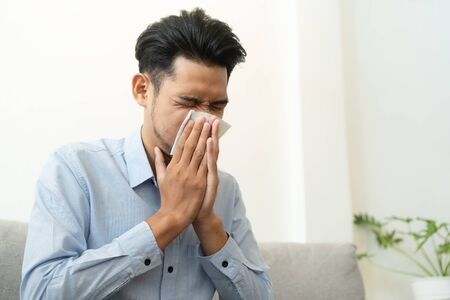 Asian handsome of  man having  flu season and sneeze using paper tissues sitting on sofa at home, Health and illness concepts Stok Fotoğraf