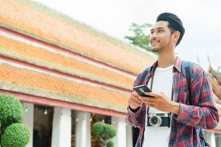 Handsome asian man tourist walking and looking smart phone at Wat Suthat Thepwararam Ratchaworawihan Bangkok, Thailand, Solo travel and backpacker concept