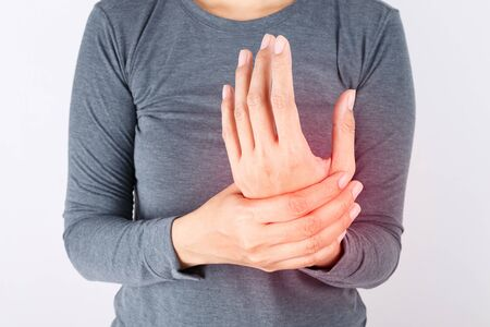 Close-up view of a woman massaging her painful hand isolated on a white background. Hands of asian young girl have inflammation