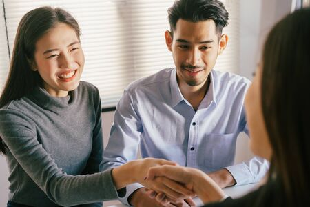 Close-up of salesman shaking hands with lovers who are customers In her office in the house purchase agreement Asian women and men smiling happily
