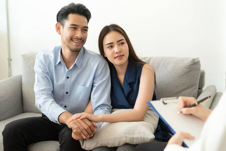 Asian couple join hand to encourage while sitting on the couch in the psychiatrist room to consult mental health problems by doctor, Health and illness concepts Stockfoto