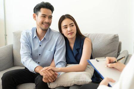 Pareja asiática une la mano para alentar mientras está sentado en el sofá de la sala del psiquiatra para consultar problemas de salud mental por médico, conceptos de salud y enfermedad