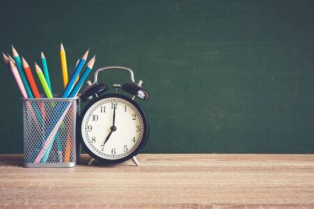 Alarm clock on wooden table on blackboard background in classroom, Back to school concept