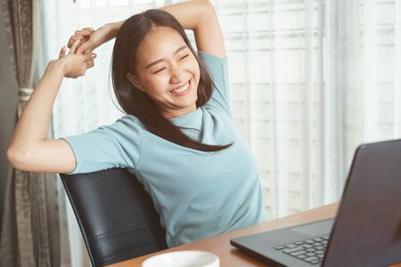 Asian girl sitting working with  laptop for long time. women is tired from working, stretching up, relaxed and smiling