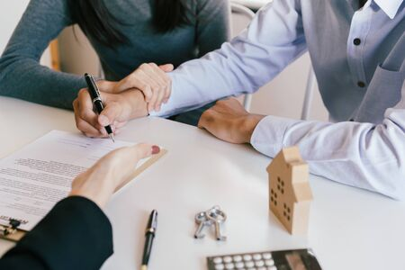 Salesmen are letting the male customers sign the sales contract house, Asian women and couple are doing business in the office, Business concept and contract signing Standard-Bild