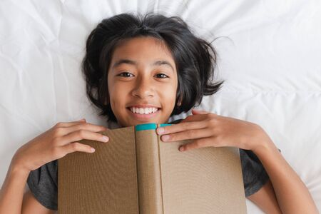 Top view of asian girl holding book brown while lying in bed, Asia little girl smile and looking at camera Reklamní fotografie