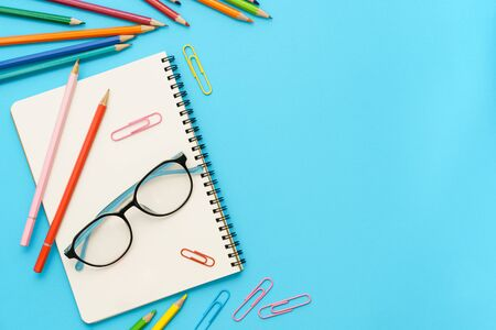 Flat lay photo of office desk with colorful pencil, Paper clip, Note book, Glasses, Top view of the copy space
