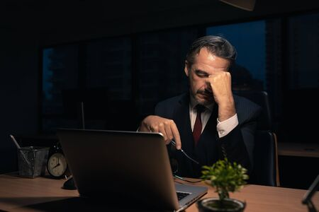 Senior male businessman in executive positions Serious And tired from overtime at the office at night , The manager is working with fatigue at night.