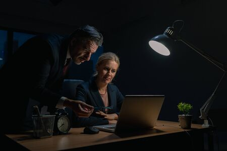 An elderly business man is advising company employees at the office during overtime , Two businessmen are discussing and solving work problems at the office at night.