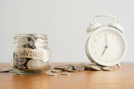 A coin in a glass bottle, a pile of coins and a white retro alarm clock on a brown wooden table. Investment business, retirement, finance and saving money for future concept.