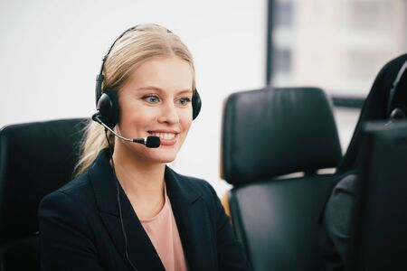 A smiling  beautiful woman sitting in a customer service department office with headset working in call centre