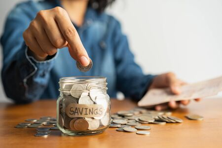 The woman hand is putting a coin in a glass bottle and a pile of coins on a brown wooden table,Investment business, retirement, finance and saving money for future concept.