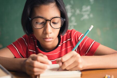 Asian girl with glasses is taking notes in her class notebook, Educational concept Reklamní fotografie