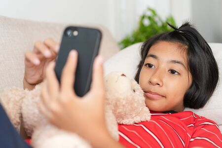Asian little girl wearing a red shirt using smartphone and smile While lying on the sofa, Doll, at her home