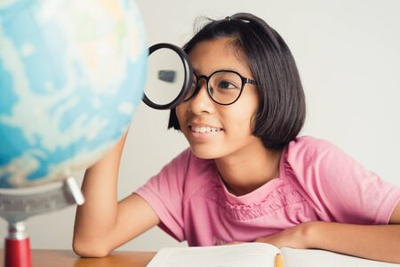 Asian girl wearing glasses is smiling and using a magnifying glass in the classroom, Educational concept
