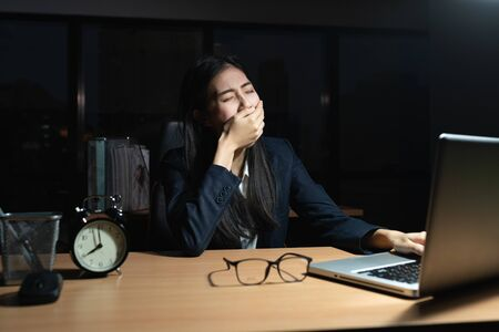 Asian business woman is sitting yawning with a hand covered her mouth, Laptop, on the desk, While the young woman works overtime in the office at night