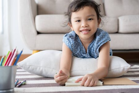 Asian  little  girl is drawing  and smile while lying on the carpet in the living room at her home