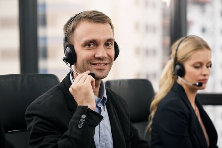 A smiling  handsome man sitting in a customer service department office with headset working in call centre  Reklamní fotografie