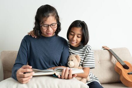 Asian mother and daughter read a book while sitting on the sofa. The little girl smiled and hugged his doll in the living room at home. Reklamní fotografie
