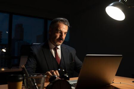 Senior male businessman  in executive positions  sitting working at office desk with laptop, While the works overtime in the office at night