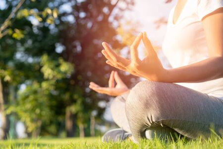 Hand of woman in lotus pose sitting on green grass and blurred background in the park, Concept of relaxation and meditation
