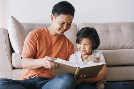 Asian father and daughter reading book while sitting in the living room at her home.