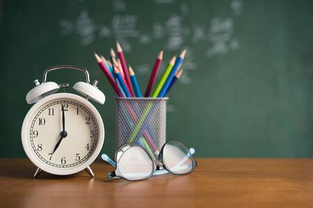 Alarm clock white and Colorful pencil, Glasses place on wooden table on blackboard background in classroom. Back to school concept