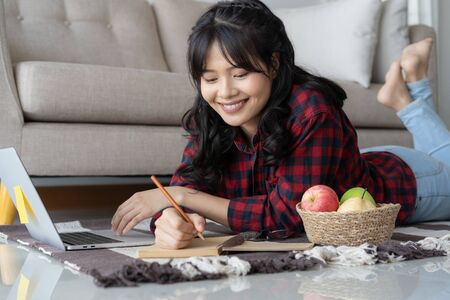 Asian woman is working are using a laptop while lying on the carpet in the living room at home. Women wearing red plaid shirt taking notes and smile