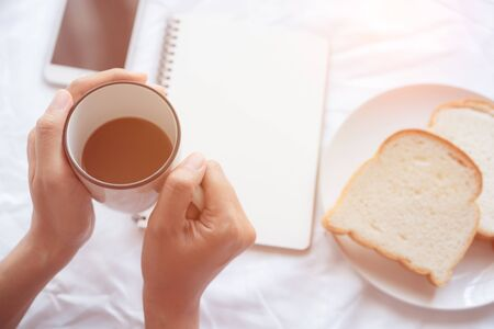 Hand of  working woman holding  cup coffee On the white table background, on the table there was bread note book and smart phone Reklamní fotografie