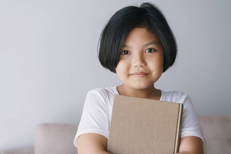 Asian  little girl is hold a brown book and smiling while standing in the living room at her home. Reklamní fotografie