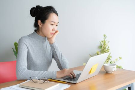 Young asian woman working on laptop in the home office desk, And sit at table resting chin on hand. Reklamní fotografie