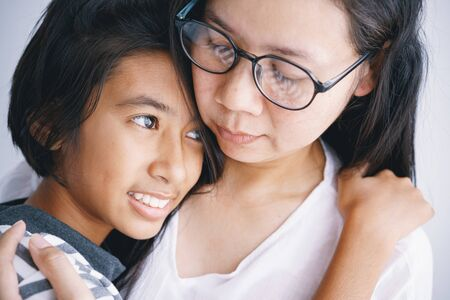 Close-up of Asian mother and daughter hugging each other with love in the room at her home