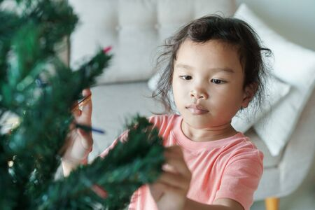Asian girl are preparing a green Christmas tree for the holiday season in her home. The little girl is decorating the Christmas tree.