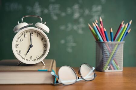Alarm clock white and Colorful pencil, Book, Glasses on wooden table on blackboard background in classroom. Back to school concept