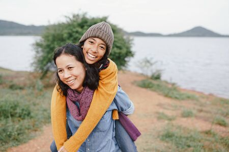 Cute Asian mother and daughter  piggyback ride on her back with the laughing  at river in the morning. The concept of  family  tourism holiday lifestyle. Stockfoto