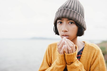 Asian  little girl wearing wool hat on river blurred background in the winter morning
