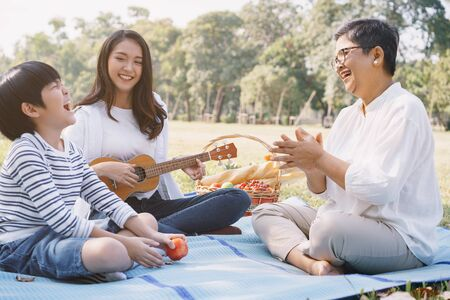 Happy Asian family having fun and enjoying while playing ukulele in the park. The concept of lifestyle in family holiday Stockfoto