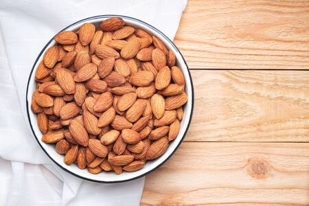 Top view of almond seeds in a bowl, on the napkin on table wooden background 写真素材
