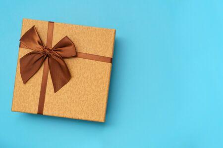 Caja de regalo marrón con cinta marrón aislada sobre fondo azul.