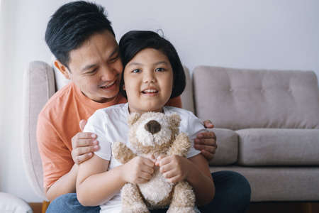 Happy Asian father and daughter playing together in the living room at home. The cute little girl hug the doll and smile happily with his father.