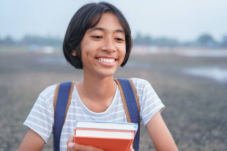 Happy Asian girl smile on face and laugh while standing Amid nature in the morning, Asia child hold book and backpack on blurred background. The schoolgirl came to study field trip and learned outdoor
