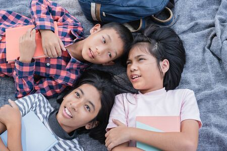 Top view. Group of Asian elementary school children talk while lying on the blanket and relaxation in the summer at park in morning. The student came to study field trip and activity learned outdoor 版權商用圖片