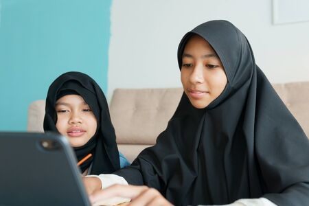 Two Muslim girl is studying online via the internet on tablet in living room at home, Asian elementary school children watching computer tablet. Concept of education at home