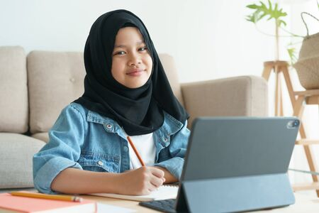 Muslim girl is studying online via the internet on tablet while in the living room at home morning, Asian elementary school children sitting write homework. Concept distance learning at home