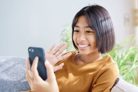 Happy Asian little girl video call on the smartphone and waving in greeting while sitting in the living room at home. Concept of relaxation and lifestyle at home