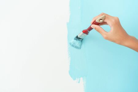 girl hand painting wall with the paint brush Close-up, Hand of young child renovation or decorating the interior home with the color blue