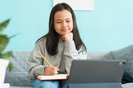 Asian little girl is studying online via the internet on tablet while sitting on sofa in living room at home. Asia children watch and write homework or practice. Concept of online learning at home
