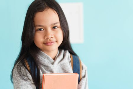 Happy Asian little girl smile on the face, Asia child hold book and backpack while standing in interior home. Portrait of a kid looking to camera. Concept backpack to school