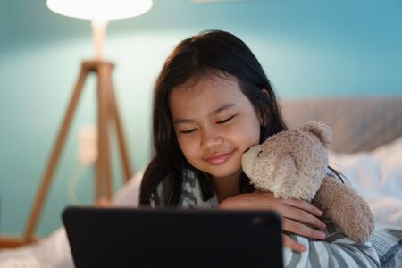 Asian little girl lying watch entertainment on a digital tablet in the bedroom at home night. Asia of child happy smile and hug dolly
