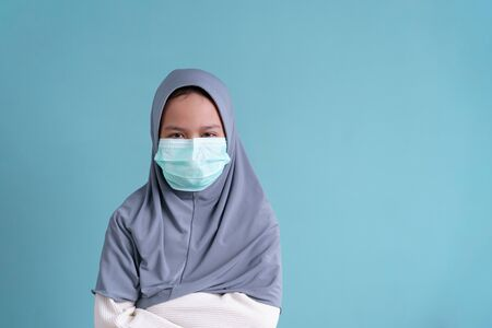 Muslim little girl wearing a protection mask epidemic of flu or COVID-19 on blue background isolated